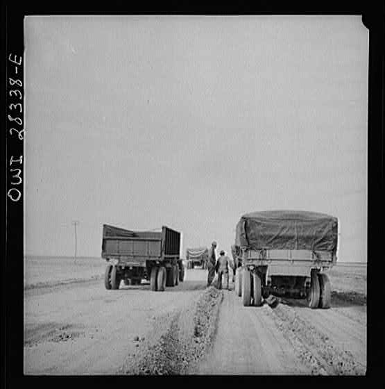 Somewhere in the Persian corridor. A United States Army truck convoy carrying supplies for Russia, moving by a disabled truck. This truck will be repaired by a crew of mechanics riding at the end of the convoy.