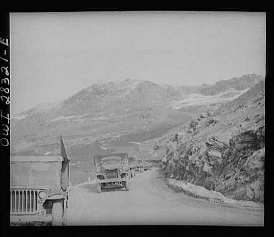 Somewhere in the Persian corridor. A United States Army truck convoy carrying supplies for the aid of Russia. Part of the convoy pulling up a mountain road. The convoy leader in a jeep at the left.