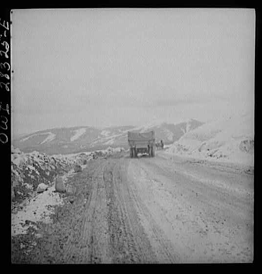 Somewhere in the Persian corridor. A United States Army truck convoy carrying supplies for the aid of Russia. A truck near the top of the snow-covered mountain making the difficult climb. An Iranian native is leading his livestock on the road.