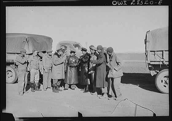 Russian officers in black leather coats surrounded by a group of American soldiers, truck drivers at a dumping spot for supplies which the Americans brought through the Persian corridor. This was one of the first all-American convoys to make the trip bringing aid to Russia. Somewhere in Iran.
