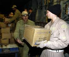 KERMAN, Iran -- Senior Airman Lindsey Whicker hands a box of water to an Iranian soldier here Dec. 28 as part of humanitarian relief efforts. Whicker is assigned to the 746th Expeditionary Airlift Squadron and was part of a C-130 Hercules crew which airlifted 20 pallets of humanitarian supplies to Iran after an earthquake destroyed the city of Bam. (U.S. Air Force photo by Staff Sgt. Suzanne M. Jenkins)